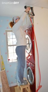 Smart Girls DIY blog - building custom shelf over stacked washer dryer how to red partition wall laundry room