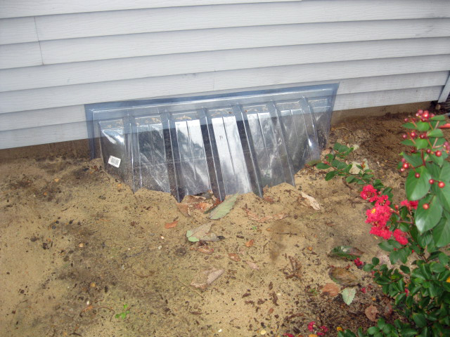 Sunken window well with cover keeping out dirt