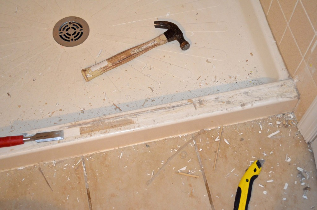 Scraping off residue with a chisel after removing shower doors