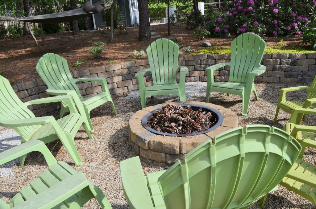 DIY backyard firepit with green plastic adirondack chairs