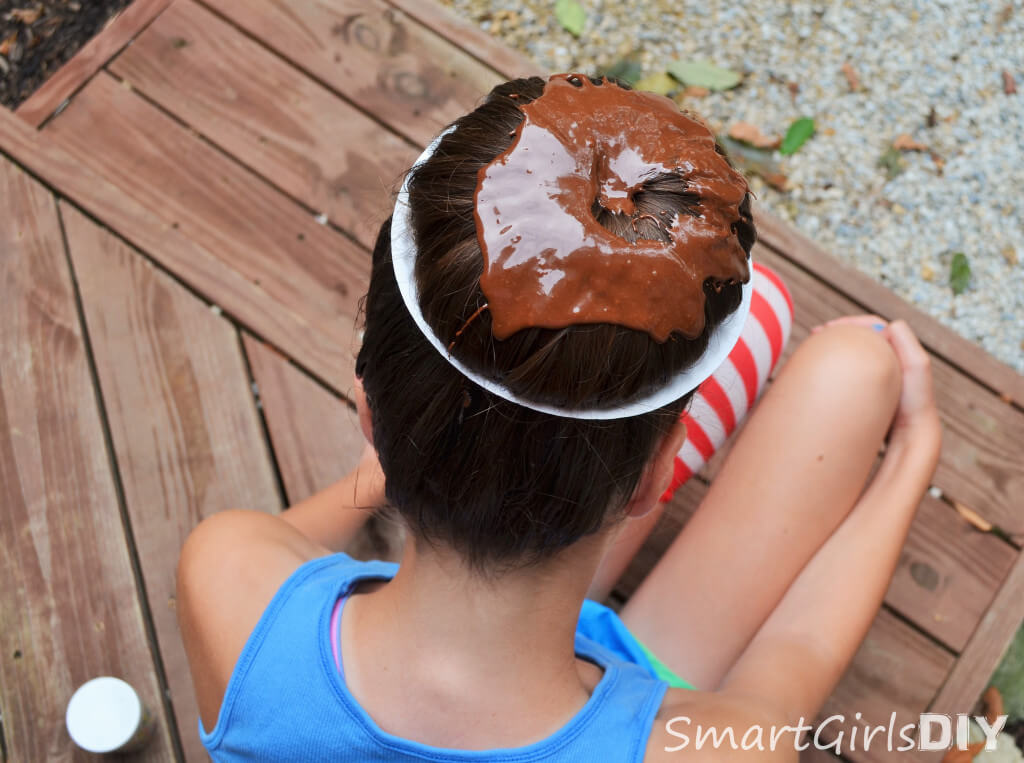 Spoon chocolate mixed with hair gel onto hair bun to make donut