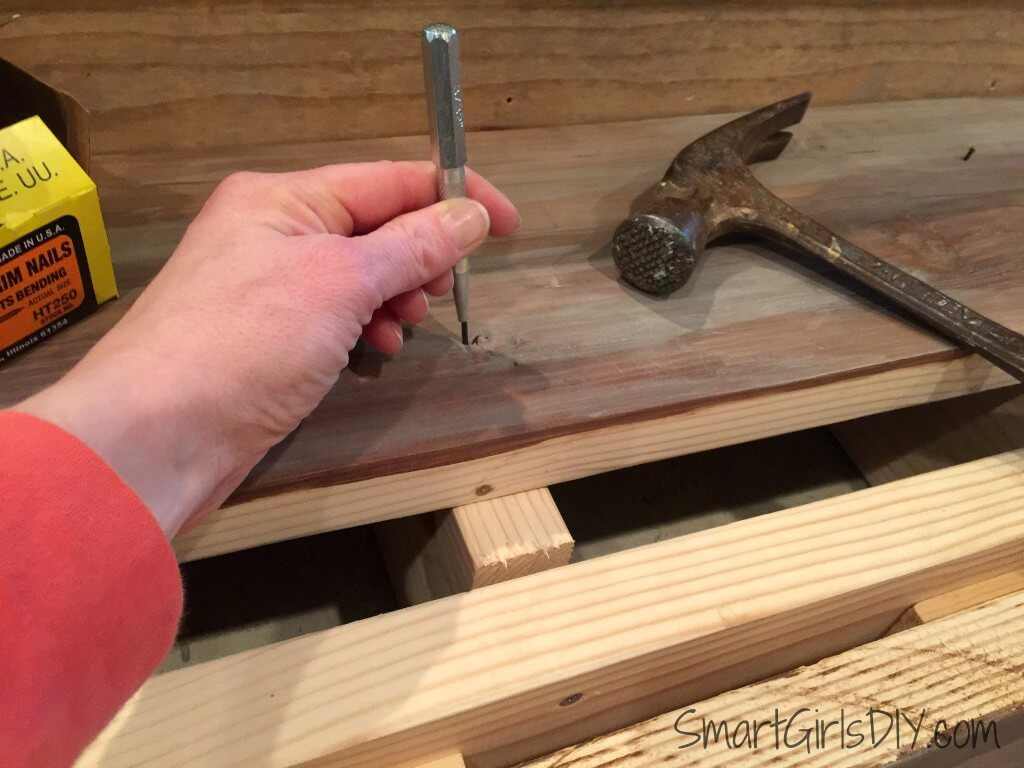 Using a nail set to --- set nails on new stair tread