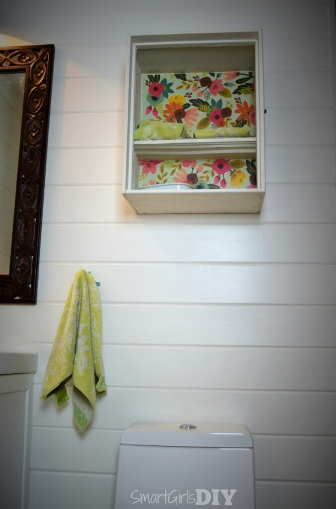 Decoupaged wall cabinet hanging in bathroom