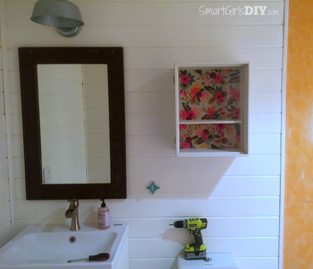 Planked bathroom walls with vintage cabinet and trim molding