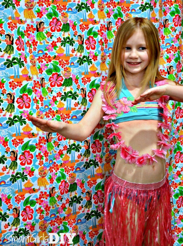 A piece of fabric thumb tacked to a wall makes for an easy Hawaiian themed photo booth backdrop